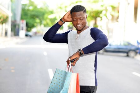 cheerful man standing in town and carrying shopping bags outdoors and looking at his watch