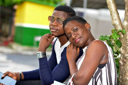 young couple sitting watching the camera smiling.