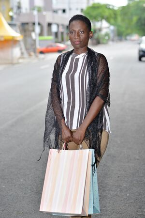 young girl standing in striped tank top on street looking at camera with bag in hand.