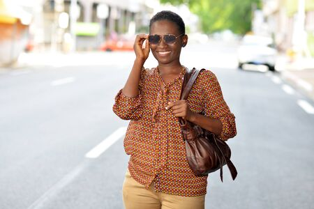 Portrait of fashionable trendy girl with sunglasses and casual wear standing in the street with handbag in hand. Copy space.