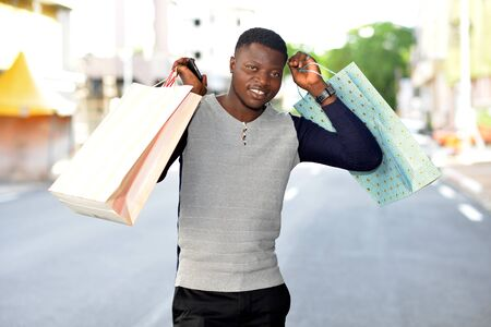 young african man standing in polo on the street and looking at camera smiling. Banque d'images