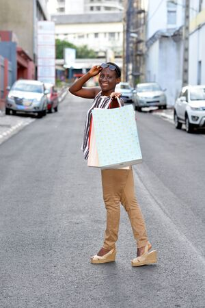 Happy and relaxed woman with colorful shopping bags walking outdoors in the city.