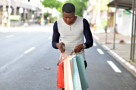 young african man standing in polo on the street and looking in bags.