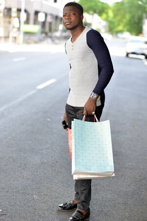 young african man standing in polo on the street after shopping and looking ahead.