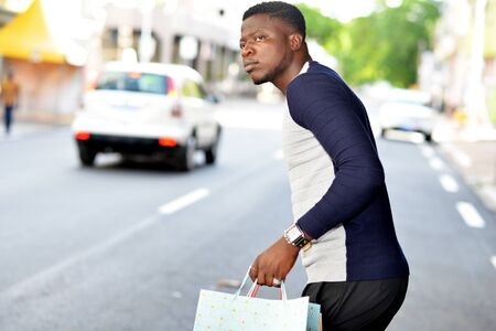 young african man standing in polo on the street and looking at the camera.