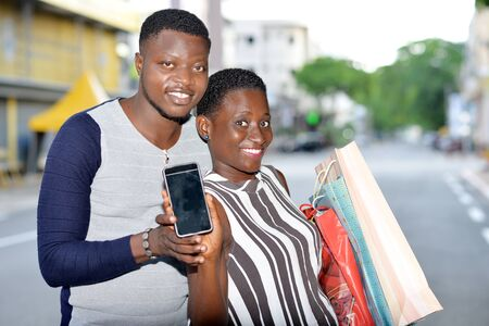 young african couple standing in the street with mobile phone looking at camera smiling.