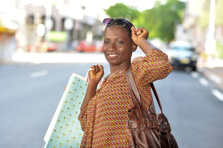 Young woman delighted with her shopping holding pile of paper bags on the street. Concepts of cost effective discount sale offer