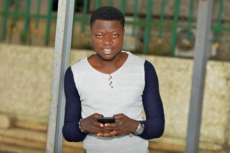 portrait of smiling young man handling a smart phone on the street while looking at the camera Banque d'images