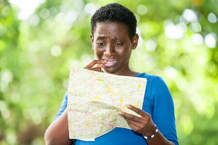 young woman standing in blue camisole looking at geographical map with strange air.