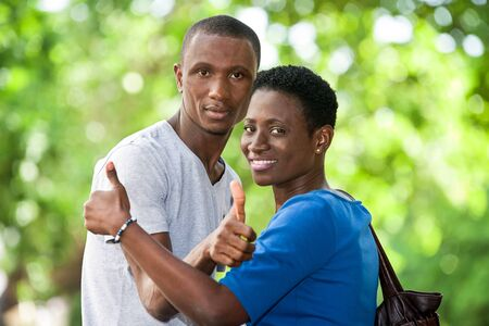 young people standing with thumb sign look at the camera smiling. Stock Photo