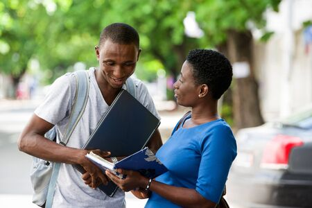 Portrait of two young students reading a book and chatting outside on campus of university