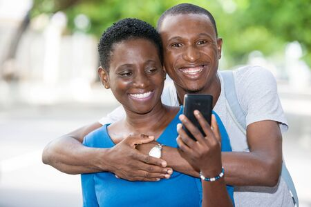 young people standing with mobile phone, embracing smiling.