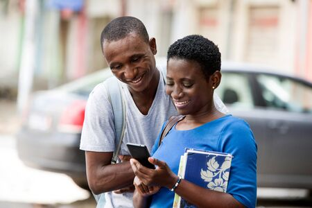 Two young happy college students standing in the street are watching and reading a message on a smart phone outdoors.