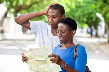 Young people standing in the street looking at geographical map with strange air.