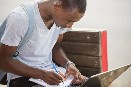 young attractive student man in the city working with laptop looking for satisfaction and confidence in the new technology and lifestyle concept of business
