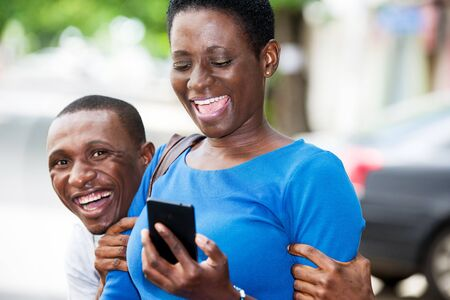 young students standing with mobile phone laughing.