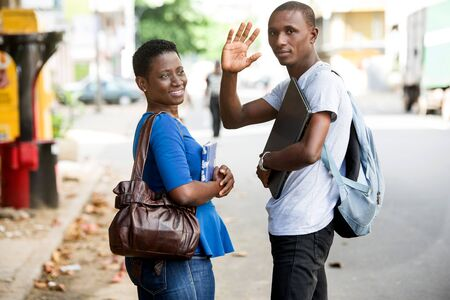 portrait of two young students waving their hands as a gesture of greeting and saying hello concept