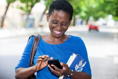 young student standing in blue t-shirt and looking at mobile phone laughing.