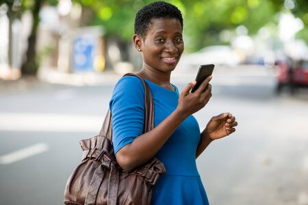 young girl standing in blue camisole with mobile phone looks at camera smiling.