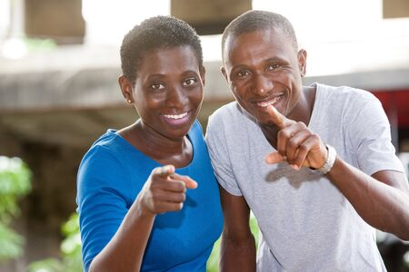 young african couple standing pointing at each other and looking at camera laughing.