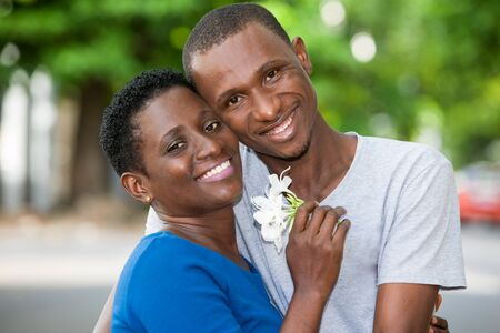 young couple standing with flower in hand embraced look at camera laughing.