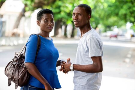 young african couple standing in street and watching the camera holding hands.