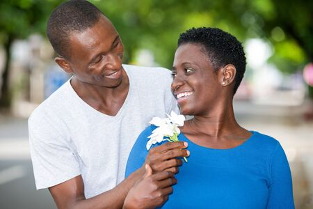 Tender young couple in love hugging blooming in the park. Happy man offering white flowers to his girlfriend.