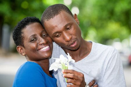 young couple standing head glued with flower in hand and smiling. Banque d'images