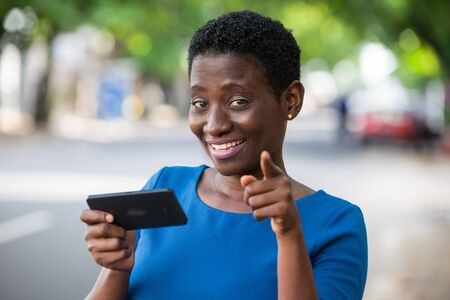 young girl standing in blue camisole cellphone in hand watching the camera smiling.