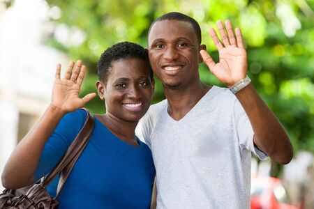 young couple standing hands raised looks at camera smiling. Banque d'images