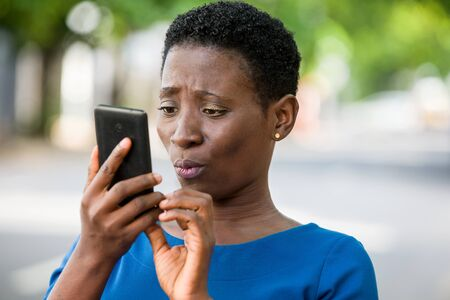 young girl standing in blue camisole looks at mobile phone with strange air. Banque d'images