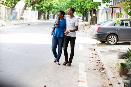 young african couple walking in the street embracing and looking in profile smiling. Banque d'images