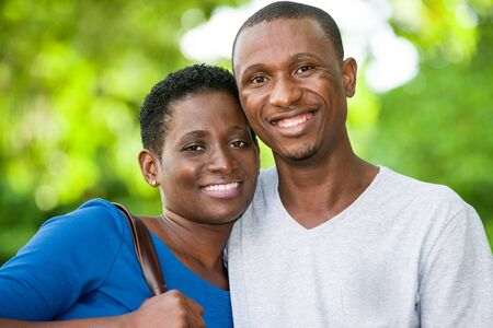 young couple standing embraced look at camera laughing.