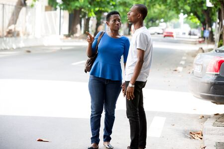 young african couple standing in street talking.
