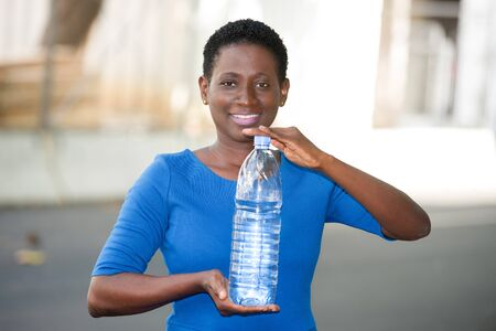 Happy woman shows a large bottle of mineral water standing alone outdoors in a sunny day