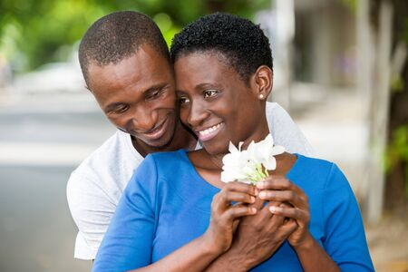 young couple standing with flower in hand smiling and embracing. Banque d'images