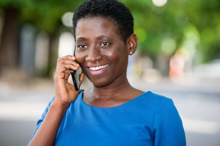 young girl standing in blue camisole with mobile phone looks at camera laughing. Banque d'images