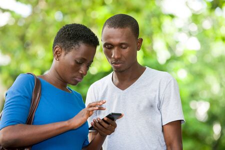 young couple standing staring at mobile phone. Banque d'images