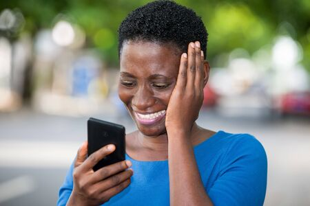 young girl standing in blue camisole looking at mobile phone laughing with hand on cheek.