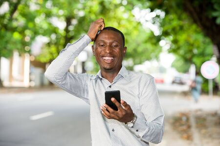 Handsome smiling man is holding mobile phone in the street outdoors and is happy with the news he has received