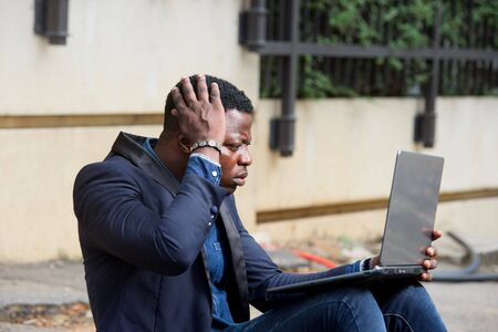 Angry, freaked businessman pulling his hair while screaming, looks bad news on laptop screen.
