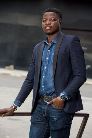 young african man standing in jacket staring smiling.