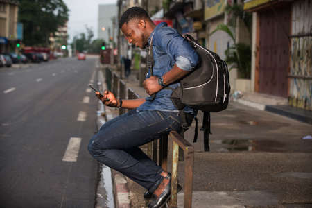young man sitting in jeans on iron bar looking at mobile phone while smiling.