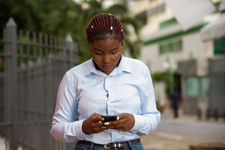 businesswoman standing outdoors working with a smart phone in the city business center