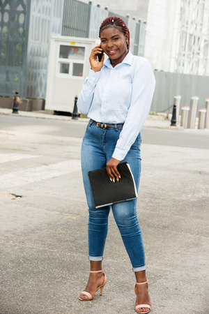 Pretty businesswoman holds paper documents and discusses financial news on smart phone on urban space