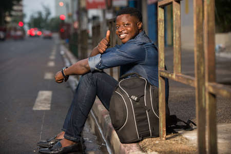 young happy traveler man with backpack, sitting alone on the street in the evening, waiting for a car or bus at the bus stop,