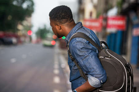young man standing in jeans backpack watching at his right side of the road.