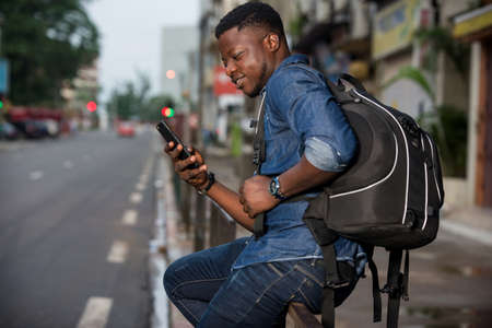 young man sitting in jeans on iron bar looking at mobile phone while smiling. Zdjęcie Seryjne