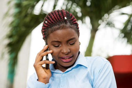Close up of young and smiling assistant talking on the phone alone outside. Connection concept