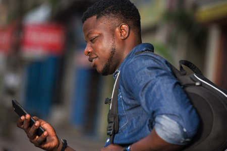 站立在有背包的牛仔裤的年轻人看手机,当微笑时。